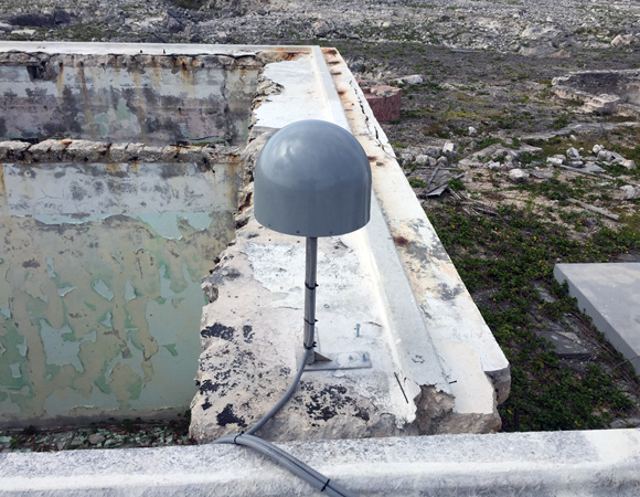The GPS antenna and mount for COCONet station CN51. The antenna was mounted on the remnants of an abandoned crew barrack. (Photo/John Sandru, UNAVCO)