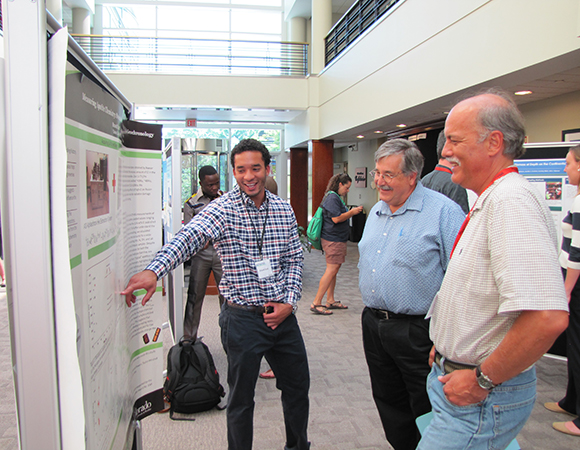 RESESS intern Brandt Scott (left) describes his work on his summer project to Rolf Norgaard (middle) and Chuck Meertens (right) at the 2015 Intern Poster Session at UCAR, July 30, 2015. (Photo/Melissa Weber, UNAVCO)