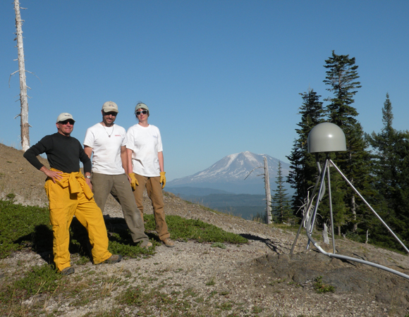 Celebrating success at station P701, Ape Canyon: Director of Geodetic Infrastructure Glen Mattioli and PBO engineers Ken Austin and Liz Van Boskirk pose with Mount Adams in the background.