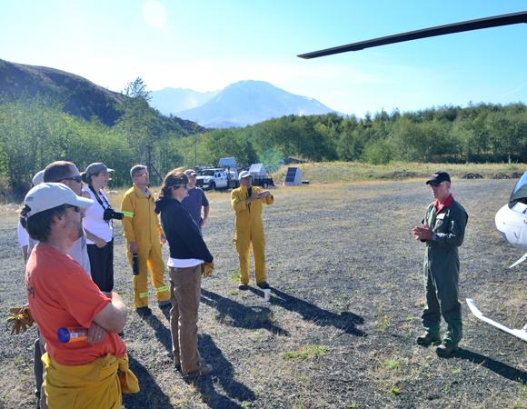 Getting ready to fly: The field team gets the helicopter safety briefing from pilot Jefferey Linscott at the staging area, with Mount St. Helens in the near distance. (Photo by Mike Gottlieb, UNAVCO)