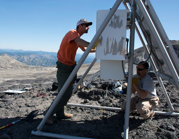 UNAVCO PBO engineers Mike Gottlieb and Chad Pyatt work to remove the 8-battery power system at station P692, Loowit Falls, in favor of a 20-battery hut. (Photo by Beth Bartel, UNAVCO)