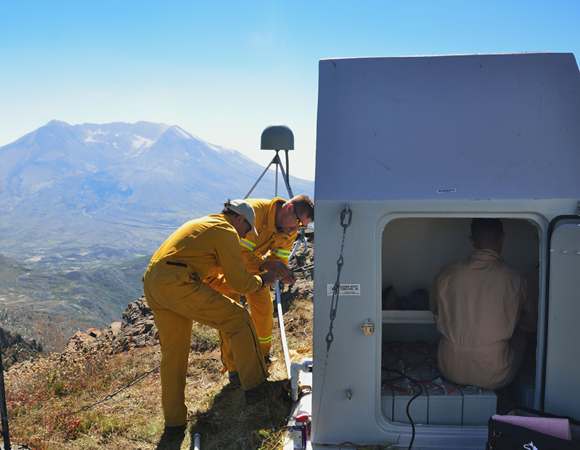 UNAVCO Director of Geodetic Infrastructure Glen Mattioli and NSF Program Director Russel Kelz work to anchor the newly installed hut at station P694, Coldwater Peak, while UNAVCO PBO engineer Chad Pyatt works to wire the batteries. (Photo by Mike Gottlieb, UNAVCO)