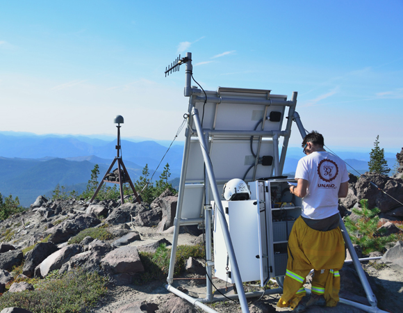 UNAVCO engineer Ken Austin works to reprogram the radio at station P698, Southeast Slope. The GPS antenna is mounted on a USGS EDM tower, the most efficient option for installing stations quickly in October 2004 shortly after unrest began. (Photo by Mike Gottlieb, UNAVCO)