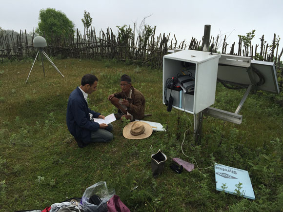 Data download at GPS station LMJG in Nepal, while landowners talk. Photo: John Galetzka,UNAVCO, May 19, 2015.