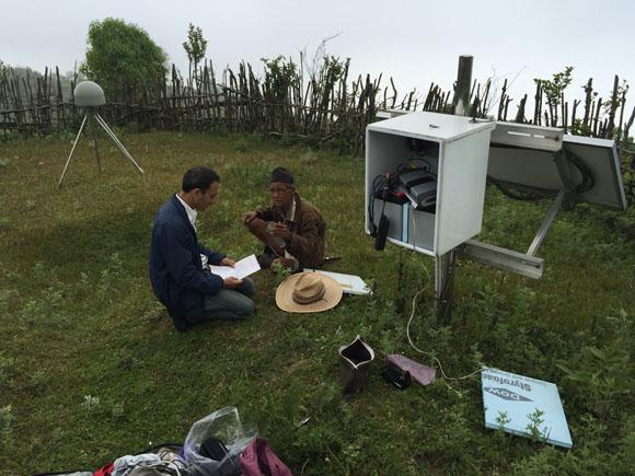 Data download at GPS station LMJG in Nepal, while landowners talk. Photo: John Galetzka,UNAVCO, May 19, 2015.
