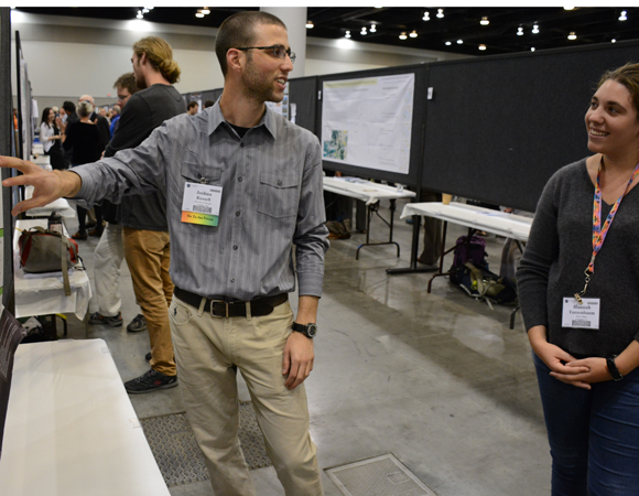 2014 intern Joshua Russell explains his summer research to a fellow attendee at the GSA Annual Meeting. (Photo/Beth Bartel, UNAVCO)