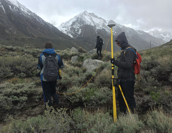Students from Indiana University survey markers on the top of the scarp of the Hilton Creek fault where it crosses McGee Creek. (Photo by Beth Bartel, UNAVCO)
