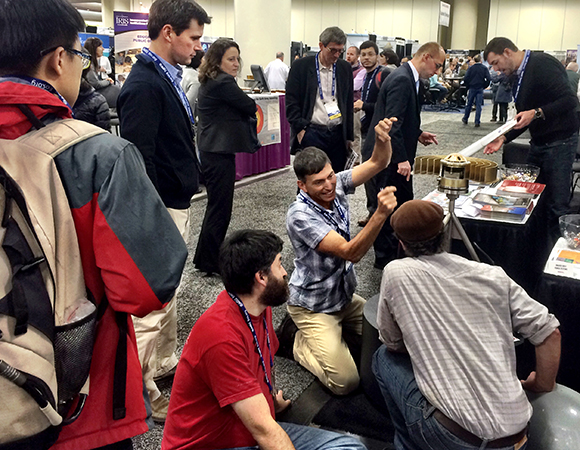 TLALOCNet project manager John Galetzka gives a lesson on GNSS antenna maintenance at the UNAVCO booth at AGU 2015. (Photo/Beth Bartel, UNAVCO)