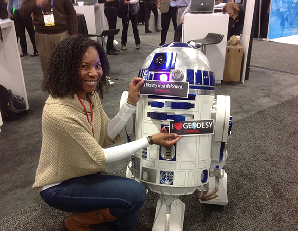 You never know just quite what you\'ll see in the exhibit hall at AGU. UNAVCO\'s Aisha Morris hangs out with R2-D2, who loves geodesy.