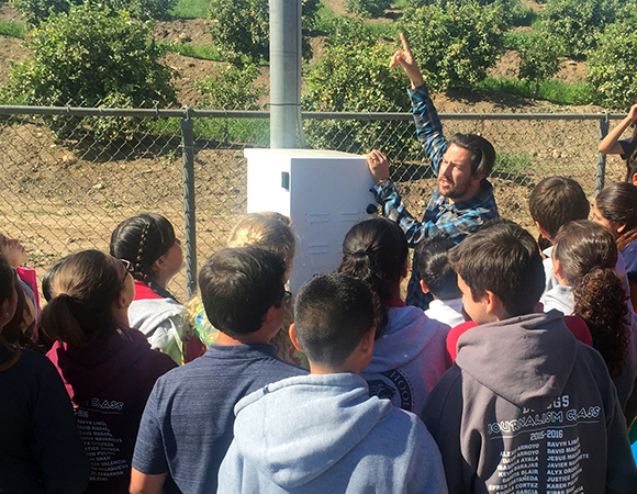 Plate Boundary Observatory Southwest Region field engineer Ryan Turner explains the GPS equipment enclosure and communications at station OVLS, hosted by Olivelands Elementary, to 7th and 8th graders from Briggs School. (Photo/Beth Bartel, UNAVCO)
