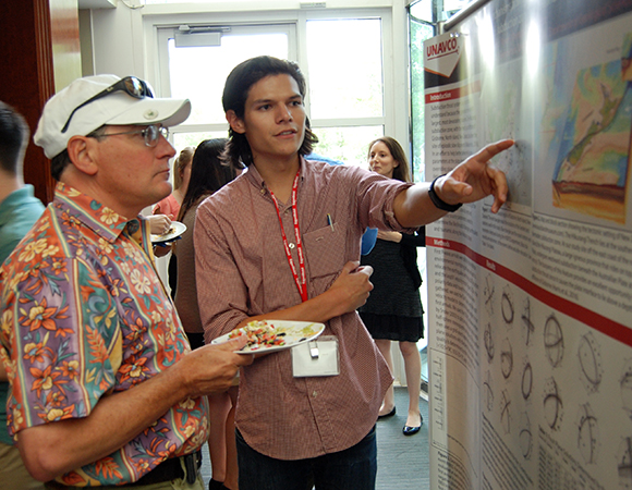 2016 RESESS intern Enrique Chon explains his summer research to Glen Mattioli, UNAVCO\'s Director of Geodetic Infrastructure. 2016 RESESS and Geo-Launchpad interns presented their summer work during a joint Front Range Intern Poster Session held at UCAR Center Green on July 28, 2016. Boulder, Colorado. (Photo/Aisha Morris, UNAVCO)