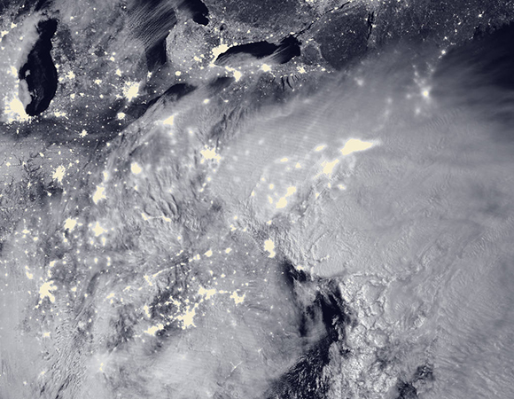 "2016 Blizzard by Moonlight: The Visible Infrared Imaging Radiometer Suite (VIIRS) on the Suomi NPP satellite acquired this image of the storm system at 2:15 a.m. EST on Jan. 23. It was composed through the use of the VIIRS ""day-night band,"" which detects faint light signals such as city lights, moonlight, airglow, and auroras. In the image, the clouds are lit from above by the nearly full Moon and from below by the lights of the heavily populated East Coast. The city lights are blurred in places by cloud cover. (NASA: http://www.nasa.gov/image-feature/2016-blizzard-by-moonlight)"