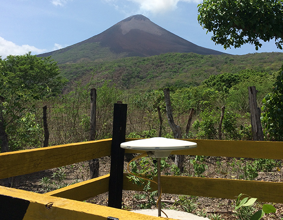 Manually downloading data and removing the wooden fence around station MOGA north of Momotombo Volcano. This semi-permanent GPS site was occupied in December 2015 in order to monitor Momotombo during its sudden eruption. (Photo/Mike Fend, UNAVCO)