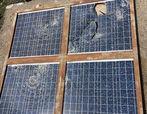 Damage from the November 22, 2015 eruption of Telica volcano. Three out of four solar panels are still partially operational, so only a 50 watt panel was required to ensure consistent power. (Photo/Mike Fend, UNAVCO)