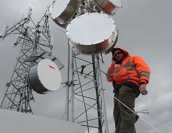 PNW: Field Engineer Adam Woolace, on a newly constructed radio tower at C059 on Steens Peak in Eastern OR, coordinates radio settings with Regional Engineer Ken Austin, 54 miles away at P393. The longest link in the network is 83 miles to P018 – one of the longest anywhere in the Plate Boundary Observatory. (Photo by Andre Basset, NSF)