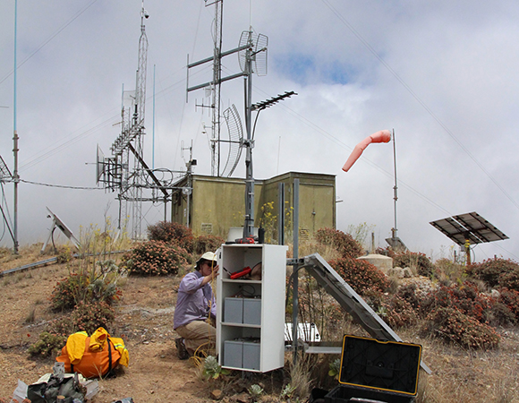 SW: Field Engineer Doerte Mann works on a radio connection from CRU1 atop Santa Cruz Island to SRS1 on nearby Santa Rosa Island. The Channel Islands are home to some of the fastest moving sites in the network. (Photo by Andre Basset, UNAVCO)