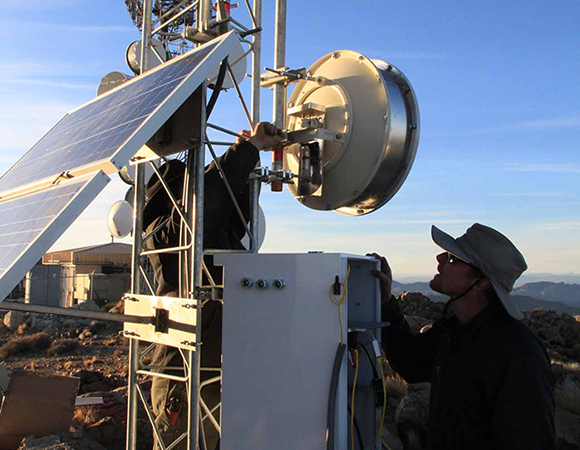 SW - Southwest Field Engineers Andre Basset and Shawn Lawrence install armored radio antennas on a newly built tower atop Rodman Mountain in the Mojave Desert. The station, RDMT, serves as a radio repeater for several nearby stations. (Photo by Ryan Turner, UNAVCO)