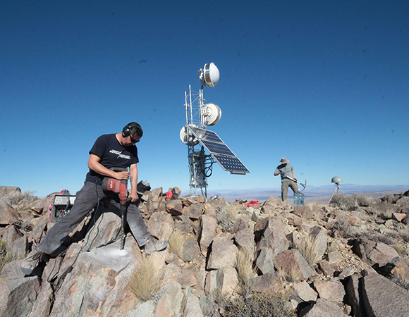 SW - Southwest Field Engineers Ryan Turner and Shawn Lawrence construct anchor points for guy wires to stabilize a newly built radio tower. Mountaintops in the Mojave often see wind speeds in excess of 100 kilometers per hour, requiring special attention to construction. (Photo by Andre Basset, UNAVCO)