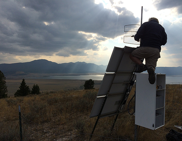 East: Field Engineer Tom Lyman dials in a new radio link at P676, just west of Yellowstone. (Photo/Tim Dittman, UNAVCO)
