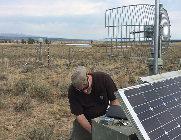 East: Field Engineer Dave Kasmer modernizes the hardware of an existing radio link at P360, just west of Yellowstone. (Photo/Tim Dittman, UNAVCO)