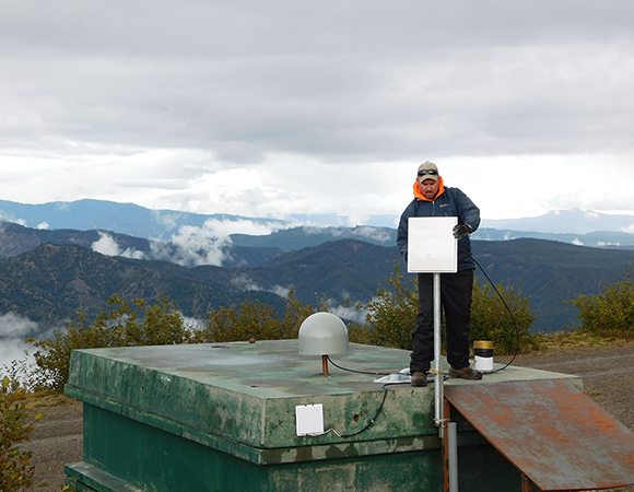 PNW: Field Engineer Adam Woolace at P694 on Mount St. Helens points a 5.8ghz panel antenna to the access point at Johnston Ridge Observatory (C054). (Photo by Russell Kelz, NSF)