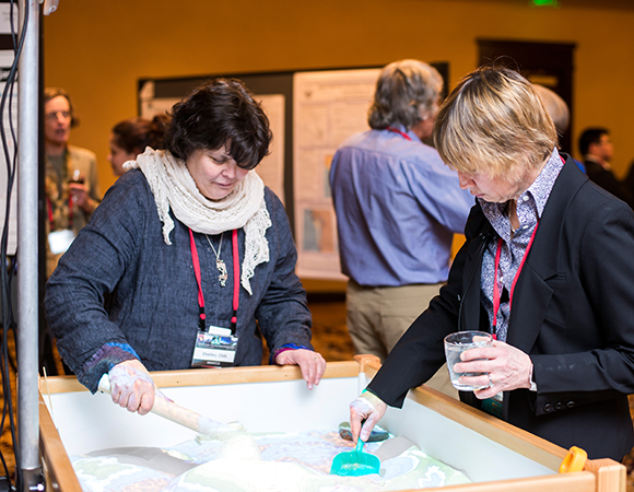 Meeting participants S. Olds and Dr. Zuber interact with the augmented reality sandbox to explore deformation. (Photo/J. La Plante)