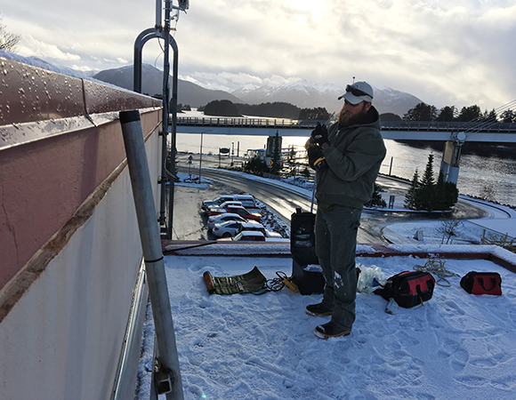 UNAVCO engineer John Sandru installs the rooftop monument for station AKSI in Sitka, Alaska. Photo provided by John Sandru.