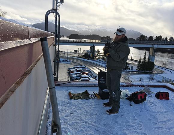 UNAVCO engineer John Sandru installs the rooftop monument for station AKSI in Sitka, Alaska. Photo provided by John Sandru.