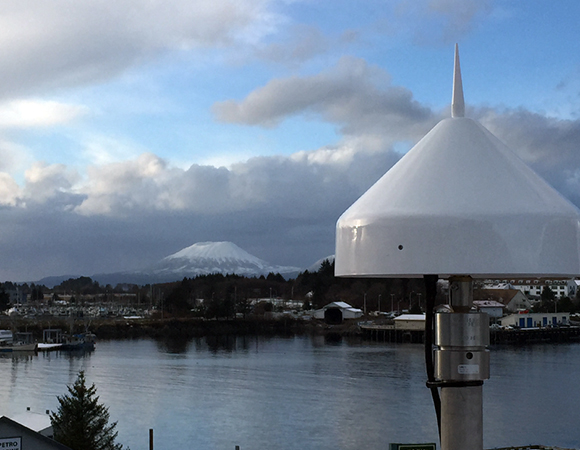 The radome for station AKSI in Sitka, Alaska protects the antenna from snow as well as nesting birds. In the background, Mount Edgecumbe. Photo provided by John Sandru.
