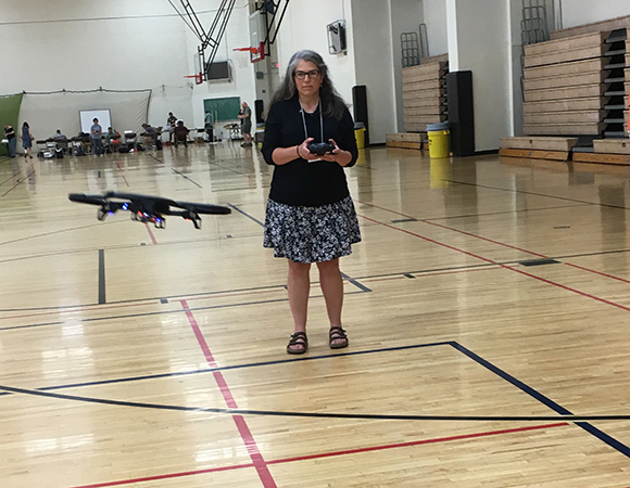 High school teacher Cheryl Manning tests a recreational drone during a hands-on activity of the Using Recreational Drones for STEM Explorations workshop at the 2017 Earth Educators' Rendezvous held at University of New Mexico, Albuquerque, NM. (Photo/Shelley Olds, UNAVCO)