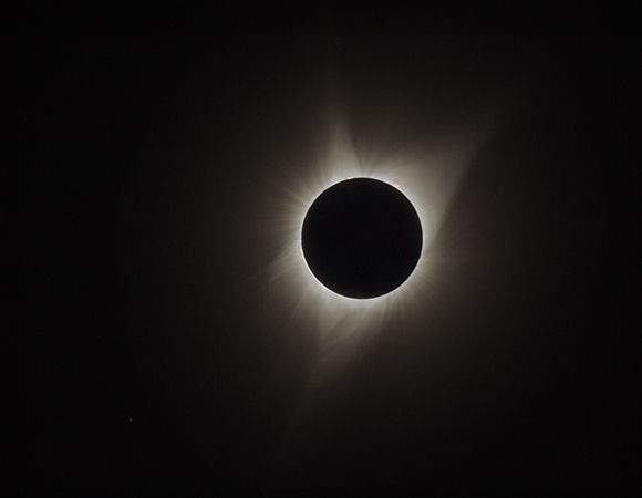 Totality during the August 21, 2017 solar eclipse, captured as a composite image using one exposure for the corona and two other exposures for prominences. The star Regulus is visible in the lower left. (Photo courtesy of Lou Estey and Brian Estey)