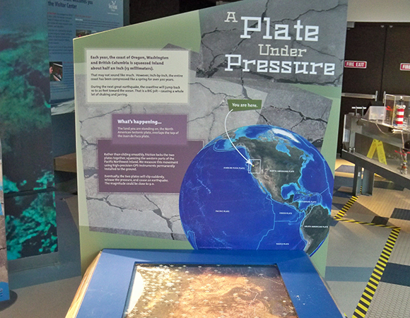 Close up of Plate Under Pressure. Visitors use the handle to compress the western edge of the map to the northeast. The crosshairs line up with GPS stations depicted on the map. Visitors observe that, similar to a compression spring, the coastal region compresses the most, further inland the land moves very little, and the eastern edge does not visibly move. (Photo/Nancee Hunter, OSU)