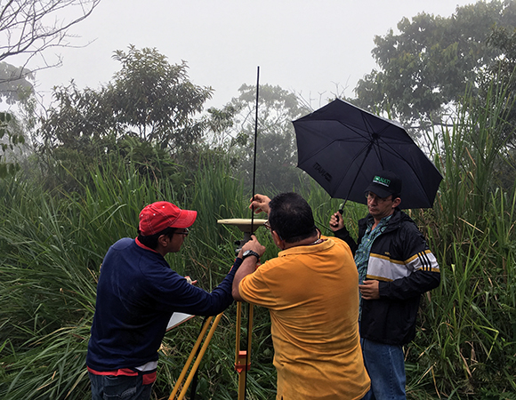 Gorki, Javier, and Omar setting up an antenna to collect episodic GPS data at station CAMP in western Panama on the border with Costa Rica, June 2017. (Photo/Mike Fend)