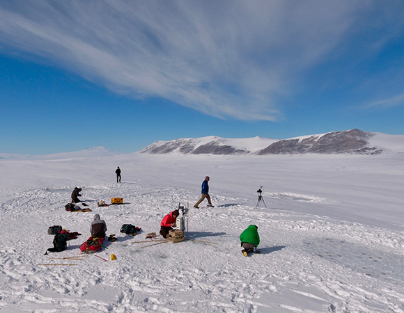 The view of a snow covered Canada Glacier with researchers hard at work constructing an experiment. The southern-most active volcano in the world, Mount Erebus, is seen in the distance. (Photo/Brendan Hodge, UNAVCO)