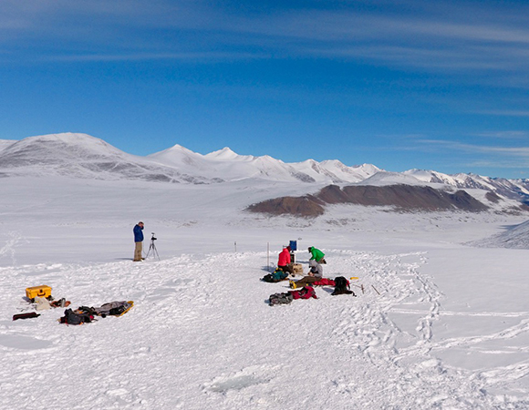The view of the Canada Glacier cryoconite study site with a view of the Taylor Valley.  The researchers are hard at work collecting data after a recent snow storm. (Photo/Brendan Hodge, UNAVCO)
