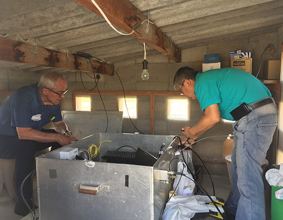 Dr. Eduardo Bergamini (left) and Yasuo Kono (right) work on the inner equipment enclosure at station CHPI.  The GNSS receiver, station computer, uninterruptable power supply, and radio transceiver are located inside the aluminum box.  The roof of the house was designed to be low in order to not block any incoming GNSS signals to the nearby antenna. (Photo/Sarah Doelger)
