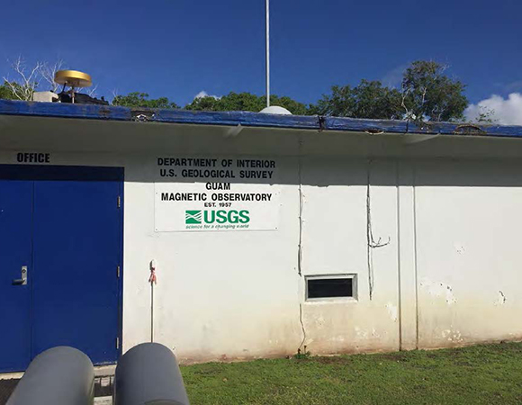 The temporary antenna (left side of rooftop, no dome) is located approximately 7 feet away from the existing IGS antenna GUAM (old opaque dome in center of roofline) and is attached to a separate receiver inside the building. The GNSS equipment is located at the Guam USGS magnetic observatory, which also operates various instruments in the area. (Photo/Sarah Doelger, UNAVCO)