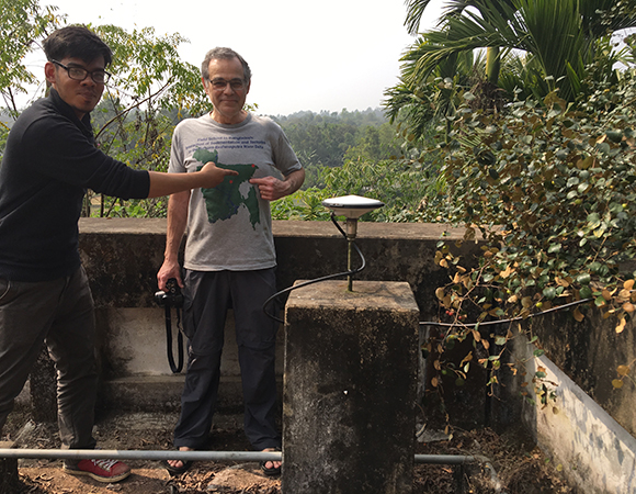 Dhaka University student Sanju pointing to where we are at on PI Michael Stekler's shirt.  Site is a reinstall at JURI that had no vegetation ten years ago. (Photo/Keith Williams, UNAVCO)