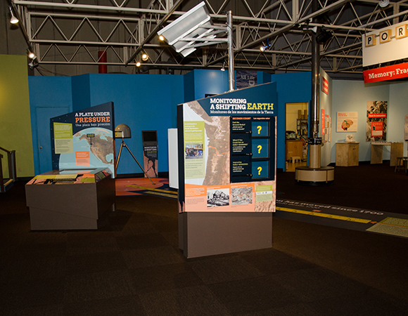 Layout of the exhibit within the Pacific Science Center. Visitors use the handle on the  Plate Under Pressure interactive to compress the western edge of the map to the northeast. The crosshairs line up with GPS stations depicted on the map. As the map is compressed, the GPS stations move away from their initial 'cross-hair' location. (Photo courtesy of Pacific Science Center)