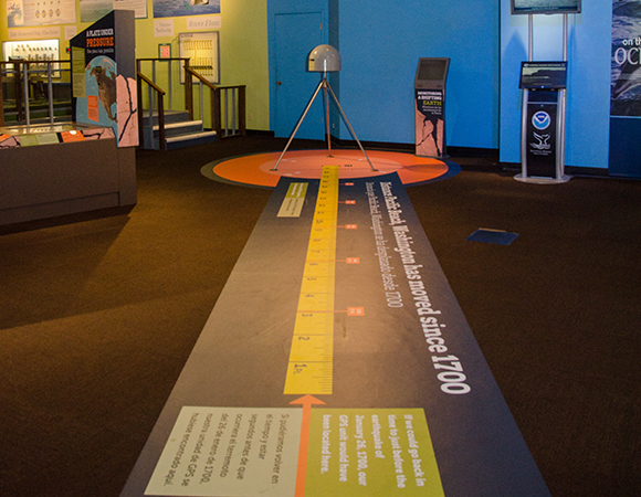 Underneath the GPS monument is a real-scale tape measuring the approximate distance that Pacific Beach, WA has moved since the previous great earthquake on January 26, 1700. (Photo courtesy of Pacific Science Center)