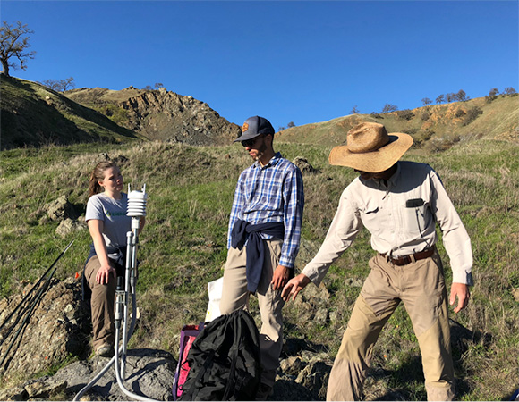 UC Santa Cruz PhD student Colleen Murphy, UC Santa Cruz PhD candidate Alex Nereson, and John Galetzka gather around the MetPack at the ORE3 cGPS station to discuss logistics for the remaining work days before hiking back to the truck. (Photo/Dylan Schmeelk, UNAVCO)