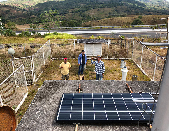 Gorki, Javier, and Omar (left to right) after compleing repairs including a new battery, GPS receiver, and solar charge controller at cGPS station CANZ, April 2018. (Photo/Dylan Schmeelk, UNAVCO)