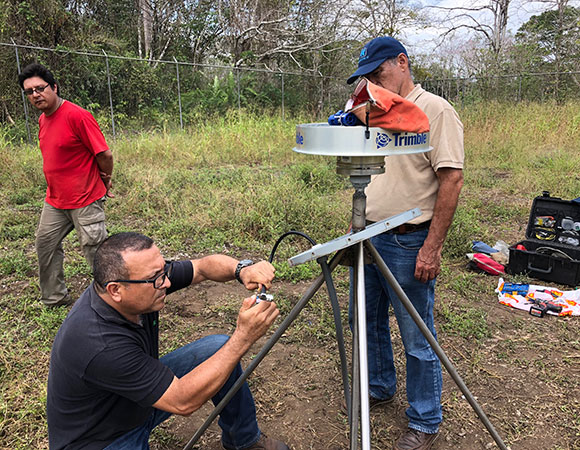 Gorki and Demetrio watch as Javier puts the finishing touches on the GPS antenna cable at what is now CN56, after the antenna was moved 25 m WNW of it's original location on top of a sinking concrete bunker (retired station CN34). (Photo/Dylan Schmeelk, UNAVCO)