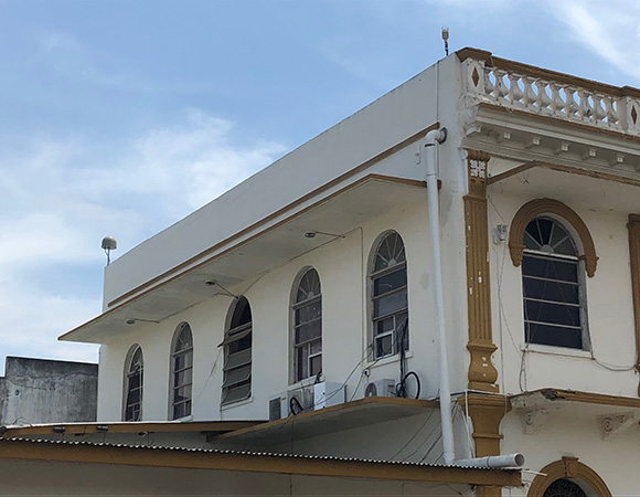 Station CN55, mounted on the Municipo de Aguadulce Building in Aguadulce. The antenna is mounted on the south (left) and metpack on the north (right) of the roof, with the GPS enclosure (bright white box) on the east-facing ledge (middle). (Photo/Dylan Schmeelk, UNAVCO)