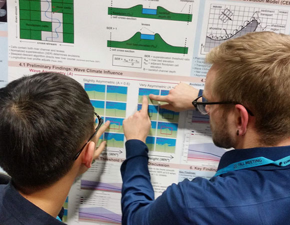2018 RESESS intern Zachary Little (right) presents his research poster to an engaged audience at the 2018 AGU Fall Meeting in Washington, D.C. (Photo/Andria Ellis, UNAVCO).