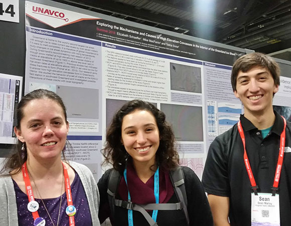 Interns Adelicia Johnson (middle) and Sean Malloy (right, USIP) support fellow intern Beth Schaeffer (left) as she presents her summer research at the 2018 AGU Fall Meeting in Washington, D.C. (Photo/Andria Ellis, UNAVCO).