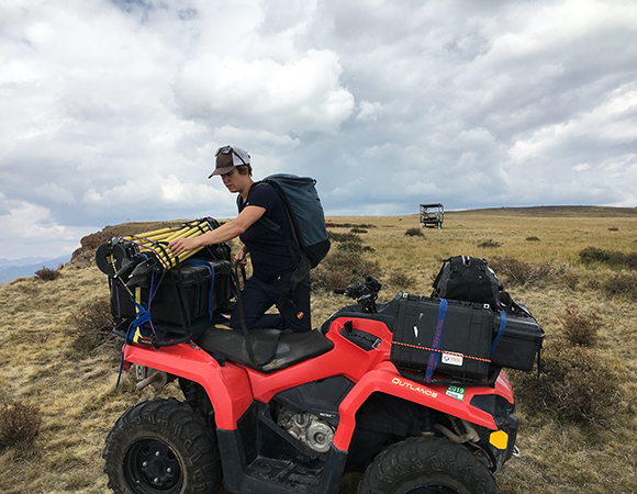 Mylène Jacquemart loads the UNAVCO TLS equipment on to an ATV for transport.  Access to the study site was provided by a use permit from the US Forest Service for scientific study of the Slumgullion landslide. An OHV trail allowed for the field team to safely and efficiently move many hundreds of pounds of sensitive instruments to the site. (Photo/Brendan Hodge, UNAVCO)