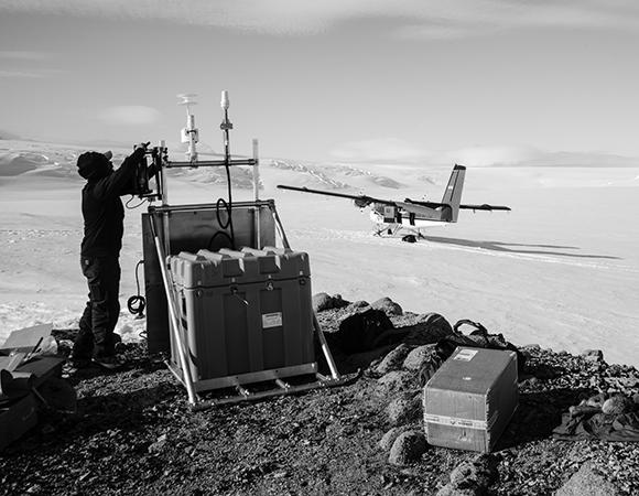 Mountaineer Mark Whetu installs the new GPS site at Gould Knoll (GLDK) on Thurston Island. (Photo/Nicolas Bayou, UNAVCO)
