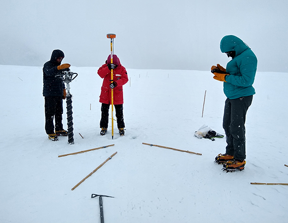 Lara Vimercati, a PhD candidate at CU Boulder, locates an experimental hole on Canada Glacier using a Septentrio Altus APS3G GNSS receiver, while Adam Solon, a PhD student at CU, waits with a Sipre Drill to drill out the cryoconite hole and Kaelin Cawley, a research scientist at the National Ecological Observatory Network (NEON), documents the field visit. (Photo/Pacifica Sommers, CU Boulder)