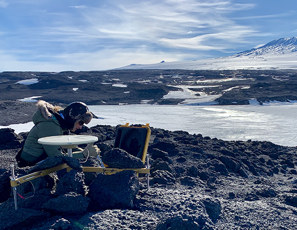 UNAVCO engineer Annie Zaino sets up a base GPS over an existing USGS benchmark with Mount Erebus in the background.  This will be used at the Cape Royds penguin colony to obtain higher accuracy measurements of the aerial survey ground control points (GCPs).  (Photo/Keith Williams, UNAVCO)